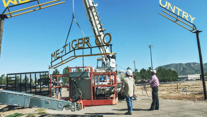 PNM workers remove the center part of the Tiger Drive archway Thursday morning.