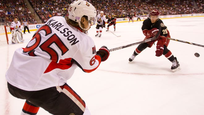 Senators defender Erik Karlsson clears the puck away from Coyotes forward Lauri Korpikoski during man Oct. 15, 2013, game in Glendale, the last time the Sens were in town.