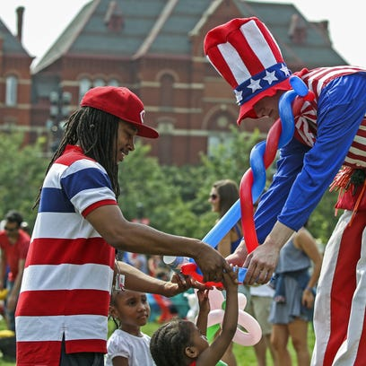 Kayden Batchelor, 2, reaches for a balloon hat made by Chad Estill, a stilt walking balloon artist for the Cincinnati Circus, during Independence Day festivities in Washington Park Saturday afternoon.