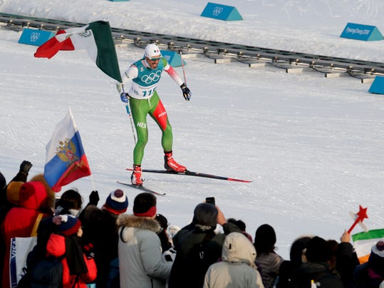 German Madrazo, of Mexico, holds up his countries flag after finishing last in the men's 15km freestyle cross-country skiing competition at the 2018 Winter Olympics in Pyeongchang, South Korea, Friday, Feb. 16, 2018.(AP Photo/Dmitri Lovetsky)