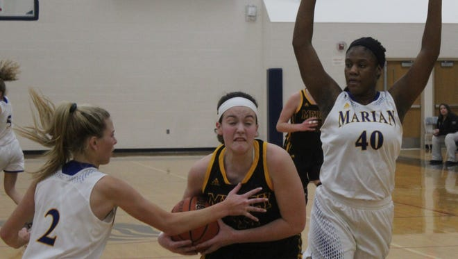Mercy freshman Julia Bishop (headband) splits Marian's defense supplied by Sophia Mancini (2) and Uche Ike (4).
