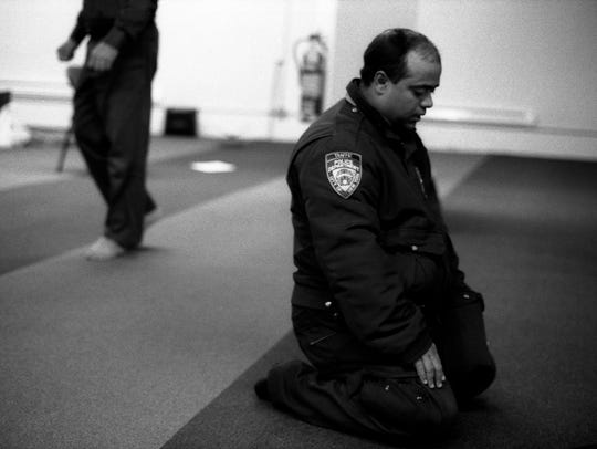 An NYPD traffic officer at prayer in Manhattan, New