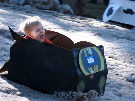 Jackson Hacker, 5, enjoys his cardboard sled ride during Festivas Saturday afternoon