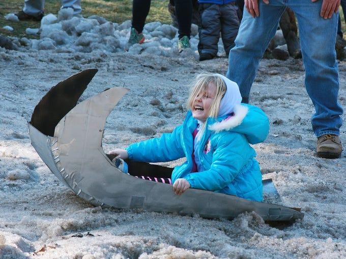 AJ Hacker, 3, enjoys her cardboard sled ride during