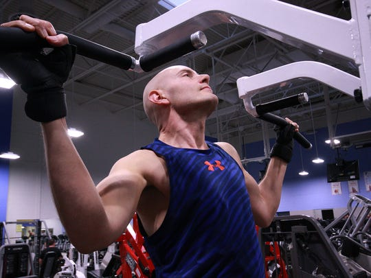 Scott Truran, a veteran with MS, uses the chip dip assist machine to work on his upper body strength at the Battle Creek YMCA.