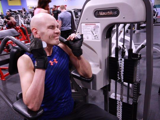 Scott Truran, a veteran with MS, works on an abdonimal machine at teh Battle Creek YMCA.