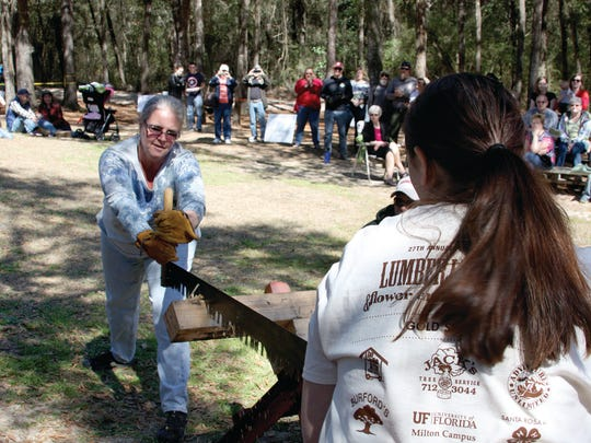 Festival goers compete in a log sawing competition at last year's Lumberjack Festival at the PSC Milton Campus.