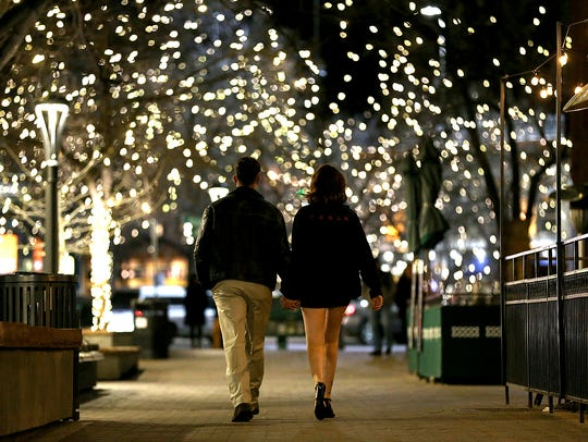 A couple holds hands as they share a romantic walk through Old Town Square on Valentine's Day in Fort Collins, Colo.
