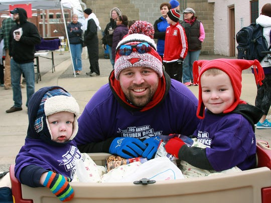 Joel Jolink with her two sons, Luke and Drew, walk during Pastrami Joe's 3rd Annual Reuben Race on Saturday with a scholarship walk for the his late wife and mother of the two boys, Kari Jolink.
