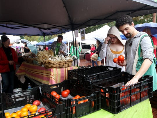 Kristen Ewbank and Ted Irvin select tomatoes from the Bird Haven Stand at the Granville Farmers Market in 2013.