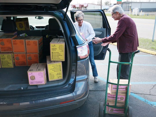 Fred Lutzke of Love Thy Neighbor helps Troop 80268 leader, Denise Demarest, unload her car full of Girl Scout cookie donations Tuesday morning.