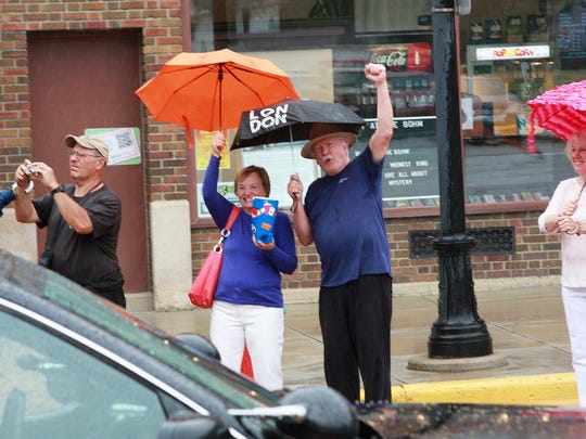 Gail and Ron Reed cheer on Marshall High School Graduates, Class of 2016, as they marched through Downtown Albion Saturday afternoon