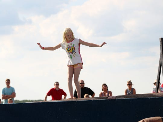 Nicole Wiley, 10, moves her feet to keep balance on a rolling log during The Great Lakes Timber Show Thursday evening.