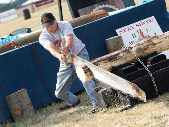 Dale Bockrath, 45, of the Great Lakes Timber Show uses a one-man saw to demonstrate older wood-cutting styles for the crowd at Field of Flight Thursday evening.