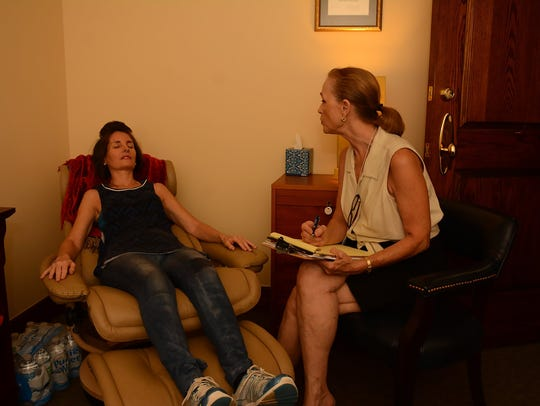 Hypnotist Carolyn Beauchamp, right, works with massage