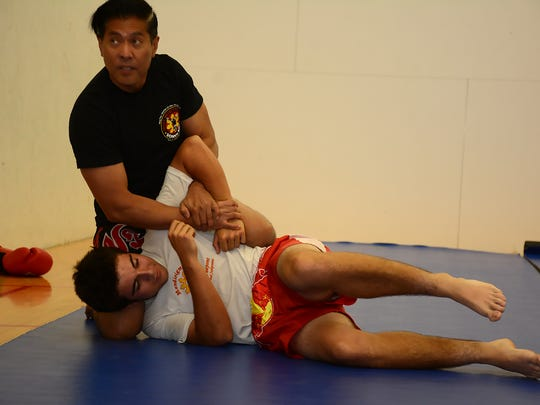 Instructor Paul Rosales, left, demonstrates a takedown  with student Thomas Harrington. City-sponsored martial arts classes are being held in the Marco Island Racquet Center during the month of August.