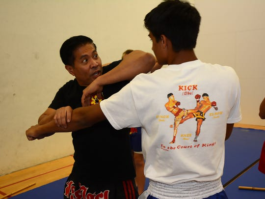 Instructor Paul Rosales, left, demonstrates an elbow strike with student Marshall Doffner. City-sponsored martial arts classes are being held in the Marco Island Racquet Center during the month of August.