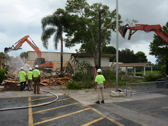 An excavator makes short work of knocking down the old building, giving a view of the 'air-nasium' behind. At noon Monday, demolition commenced for the old community center at Mackle Park. Within a year, the building will be replaced by a larger, modern structure.