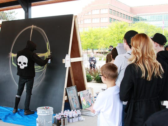 A crowd watched street artist Hope begin a mural at Color the Creek on Saturday at McCamy Plaza's Festival Market Square.