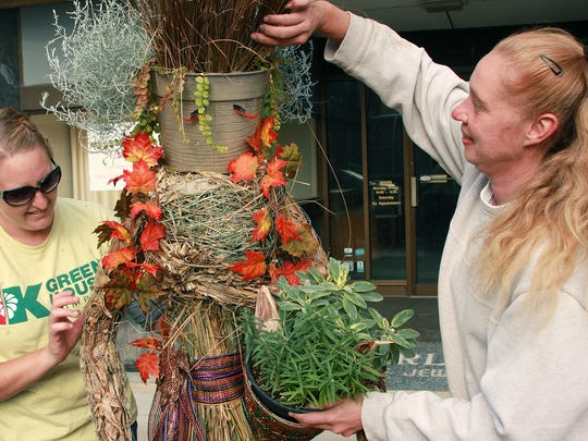 Vanessa Irving and Kathy Rewalt with K Drive Greenhouse put the last finishing touches on Harvest Goddess, their all-natural scarecrow, Wednesday afternoon.