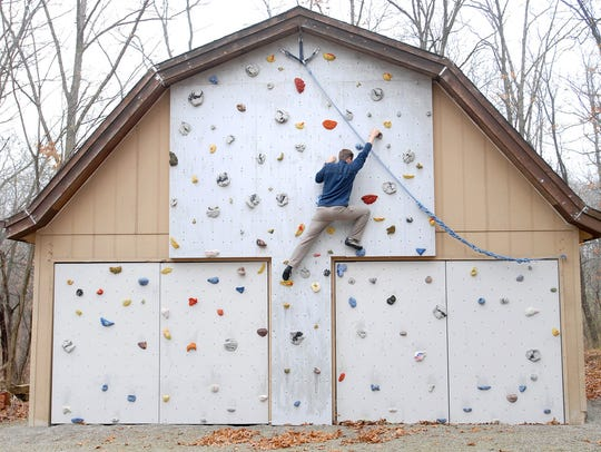 Matthew Fienup climbs a wall at the home of a client