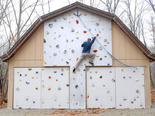 Matthew Fienup climbs a wall at the home of a client in Fairfield, Iowa.