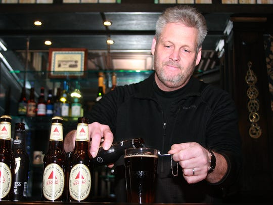 Kelly Williams pours Guinness to make a black and tan at the Franke Center for the Arts in Marshall.