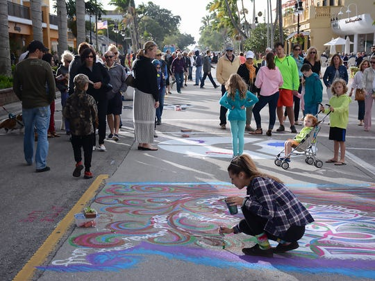 """Darby Nerl works on her """"canvas."""" Thousands walked Fifth Ave. South on Jan. 23, 2016 to view artwork created directly on the street in Chalk Art 2016, presented by the Pelican Bay Rotary Club."""
