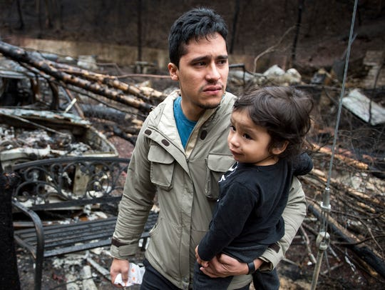 Allan Rivera holds onto his son Nathan Rivera, 23-months-old,