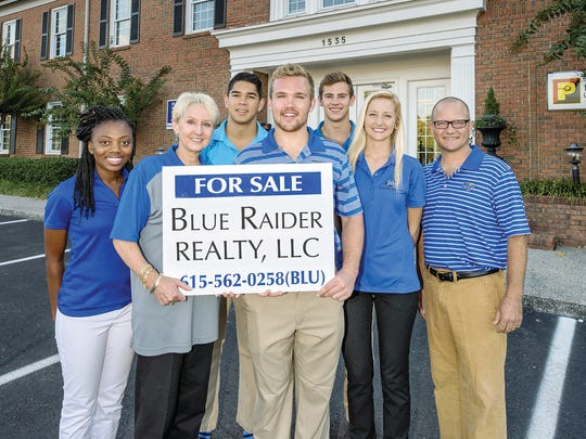 Blue Raider Realty managing broker Kathy Jones (center, holding sign) with MTSU real estate students (l to r) Nija Threat, Mark Dunn, Cayman Seagraves, Daniel Vincent, and Jennifer Mayberry, along with professor Philip Seagraves (far right) outside the Parks Group offices in Murfreesboro.