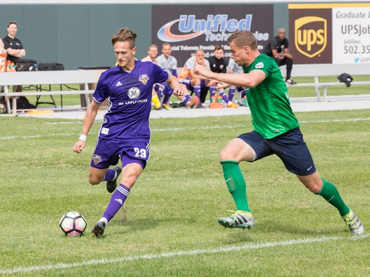 Louisville City rookie Richard Ballard takes on a Saint Louis FC defender