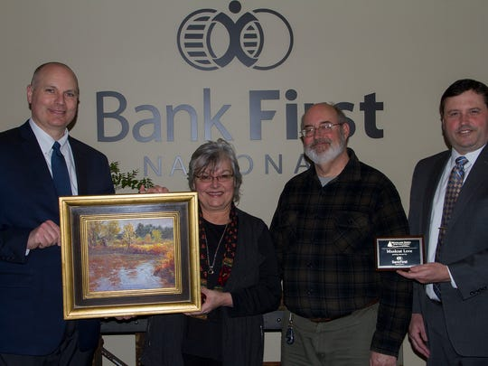 "Dennis Tienor (from left) of Bank First, Bonnita Budysz, Woodland Dunes Nature Center Executive Director Jim Knickelbine and Jeff Zimmerlee of Bank First. Teinor donated the painting, ""Muskrat Love,"" framed in an organic, artisan style by local artist, Robert Theaker, to Woodland Dunes Nature Center."