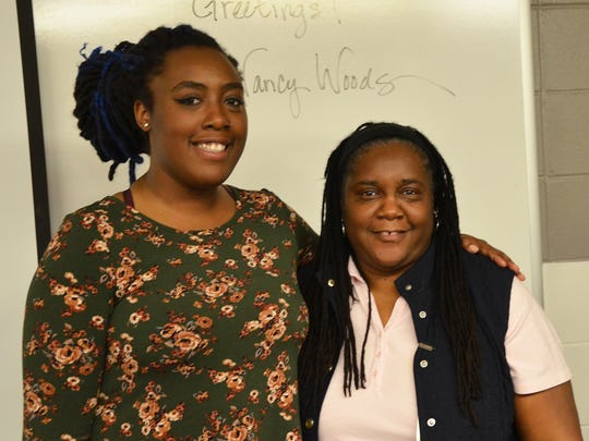 Rashida Anderson-Abdullah, left, stands with her mother Marie Anderson after a surprise announcement that Rashida had won the Jack Kent Cooke Foundation Undergraduate Transfer Scholarship on Thursday, April 13, 2017 at the Ankeny DMACC campus.