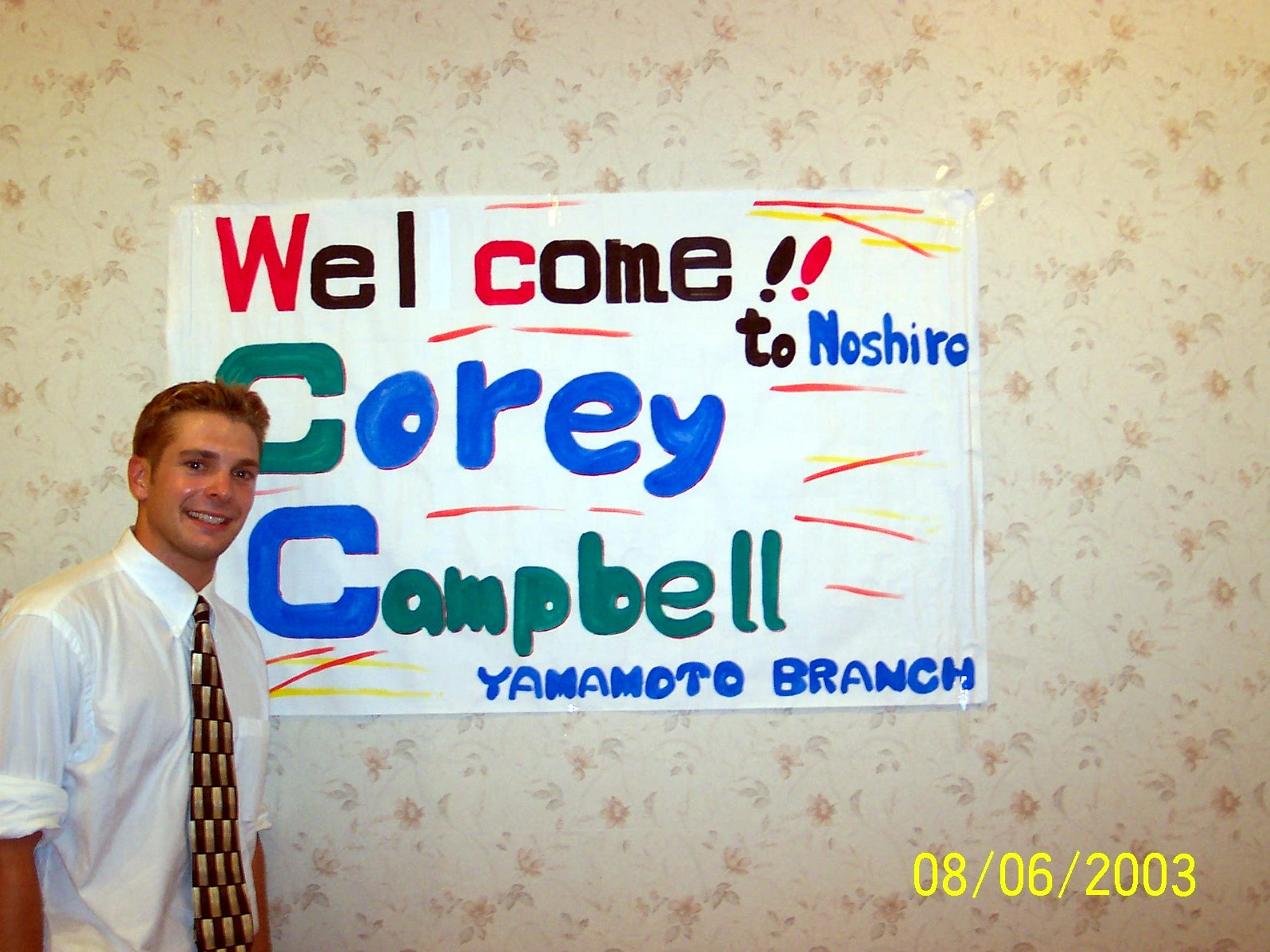 """Corey Campbell stands next to sign welcoming him to Japan, where he spent three years teaching  English in various schools. Campbell loves the sign because someone had added an extra """"l"""" to Welcome at first, then had to white it out."""