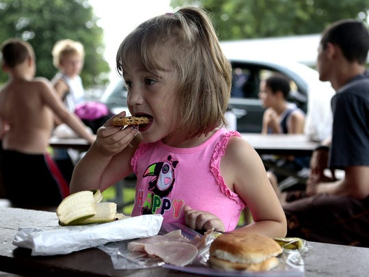 The Summer Food Service Program is sponsored through the U.S. Department of Agriculture and run locally through the Salvation Army. Kayeleigh Cochran, whose mother volunteers with the program in Buckeye Lake, eats one of the lunches in this 2014 file photo.