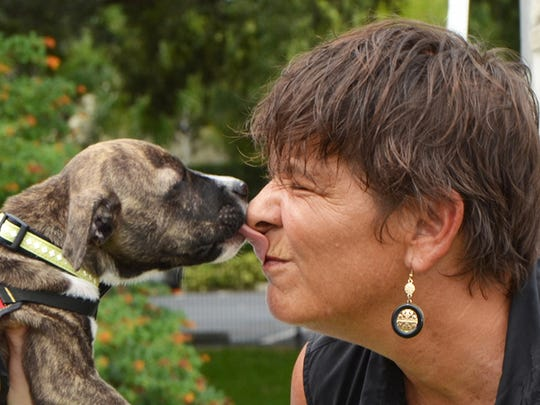 Jennifer Ross, morning co-host of Sunny 107.9 FM, catches a kiss from one of the adoptable shelter animals. She will emcee the Mutt March festival again this year.
