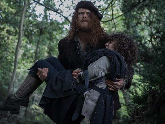 "Jamie carries Fergus (Romann Berrux) in a scene from Season 3 of ""Outlander."""