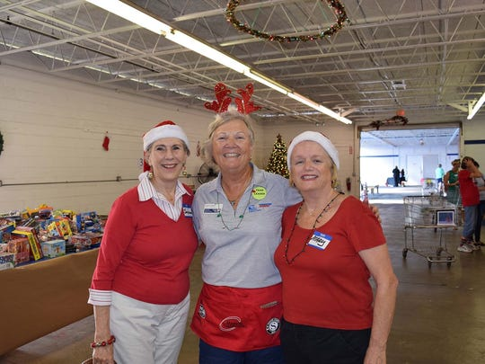Volunteer elves Suzanne Horstman, left, and Mary Sawyer, right, assist United Way Director of Community Engagement Lucy Corley, center with toy distribution during the White Doves Holiday Project last year.