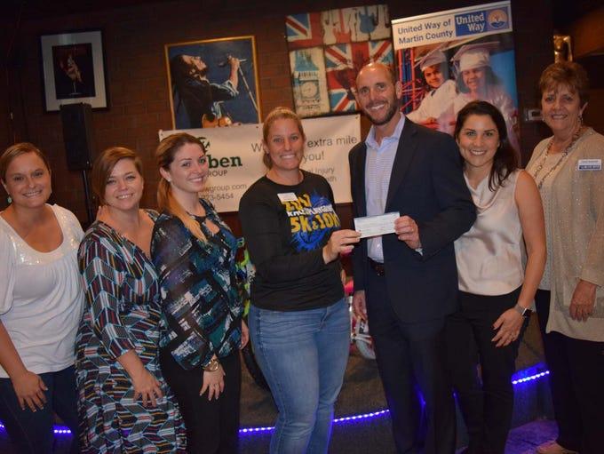 The Junior League presents a check to the Zweben Bike