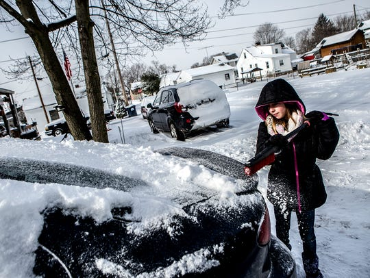 Neveah Mitchell, 10, cleans the snow off her family's