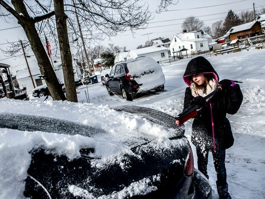 Neveah Mitchell, 10, cleans the snow off her family's car before headed out to go sledding on January 13, 2017.