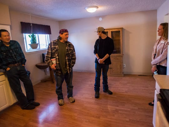 Neighbor to Neighbor Executive Director Kelly Evans, right, visits with  James Park, left, Aaron Letner, middle, and Evan Schockley while giving a tour of one of three N2N homes being shared by formerly homeless individuals with low-incomes and some form of disability.