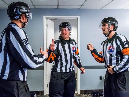 Linesman Jake Davis (23), referee Tim Mayer (19) and