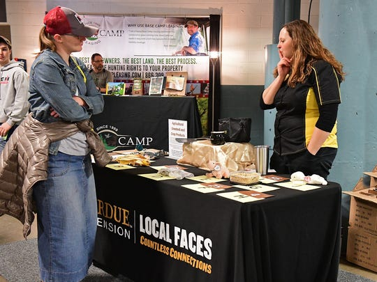 A Fort Wayne Farm Show visitor takes a look at the agricultural products game at the Purdue University Extension Service booth while an Extension employee answers her questions during the first day of the 2018 Fort Wayne Farm Show.