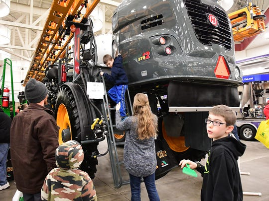 Big farming equipment was of interest to the adults considering a purchase and also to the kids who used as them as climbing jungle gyms during the 2018 Fort Wayne Farm Show.