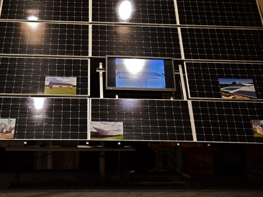 A Renewable Energy Systems solar panel display with built-in photos showing the panels installed at several farms in the area.