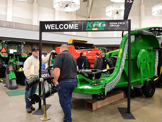 Two men discuss a shiny new pasture mower at the Farm Show.