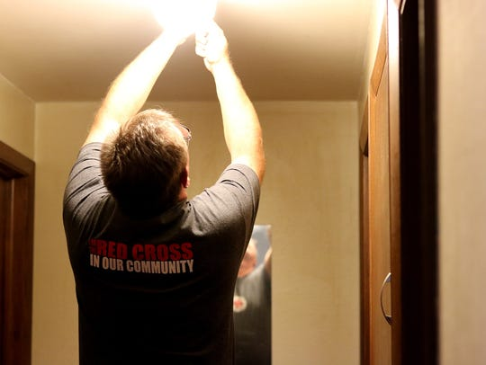 A Red Cross volunteer installs a smoke alarm in the home of a Meals on Wheels participant in Sheboygan County.