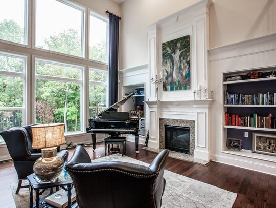 Built-in bookshelves, a fireplace and large windows
