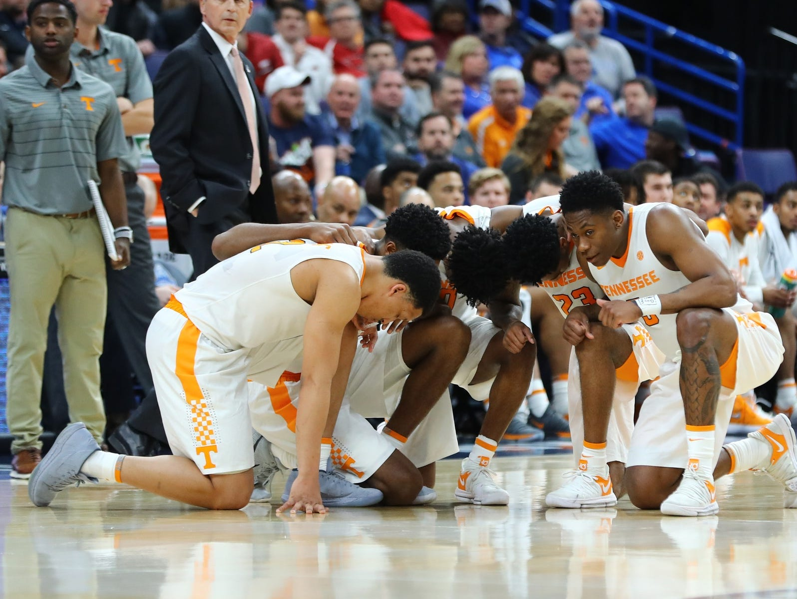 The Tennessee Volunteers take a knee as trainers examine injured Mississippi State Bulldogs player Nick Weatherspoon (not pictured) during the second half of the quarterfinals in the SEC Conference Tournament at Scottrade Center. Mandatory Credit: Billy Hurst-USA TODAY Sports